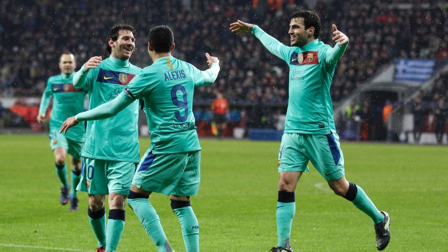 Barcelona's Alexis Sanchez, center, celebrates scoring a goal with team mates Lionel Messi, left, and Cesc Fabregas, right, during the Champions League round of the last sixteen soccer match between Bayer 04 Leverkusen and FC Barcelona  Tuesday, Feb. 14, 2012 in Leverkusen, Germany. (AP Photo/Frank Augstein)