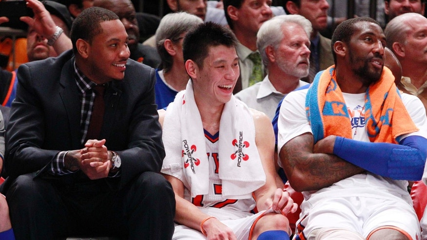 New York Knicks' Jeremy Lin, center, talks with teammates Carmelo Anthony, left, and Amare Stoudemire, right,  Wednesday, Feb. 15, 2012, in New York.  (AP Photo/Frank Franklin II)