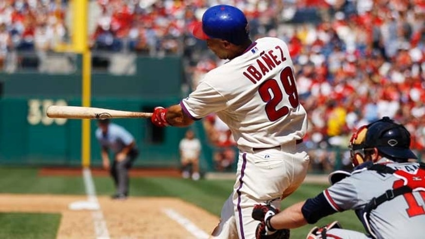 Philadelphia Phillies' Raul Ibanez follows through on a two-run single in the seventh inning of a baseball game against the Atlanta Braves, Sunday, July 10, 2011, in Philadelphia. At right is Braves catcher Brian McCann. The Phillies won 14-1. (AP Photo/Matt Slocum)