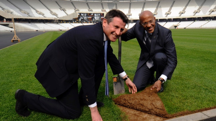 File - Former British athlete and head of the LOCOG, Sebastian Coe, left, assists former Namibian athlete and Chairman of the IOC Athletes' Commission Frank Fredericks lay the final turf in the London 2012 Olympic stadium,  London, in this Tuesday, March 29, 2011 file photo.