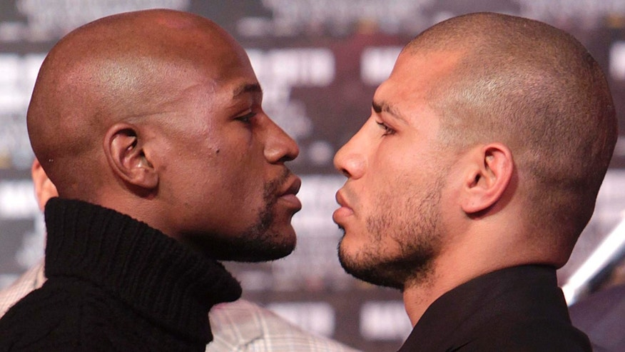 Boxers Floyd Mayweather, left, and Miguel Cotto face-off during a news conference in New York, Tuesday, Feb. 28, 2012.