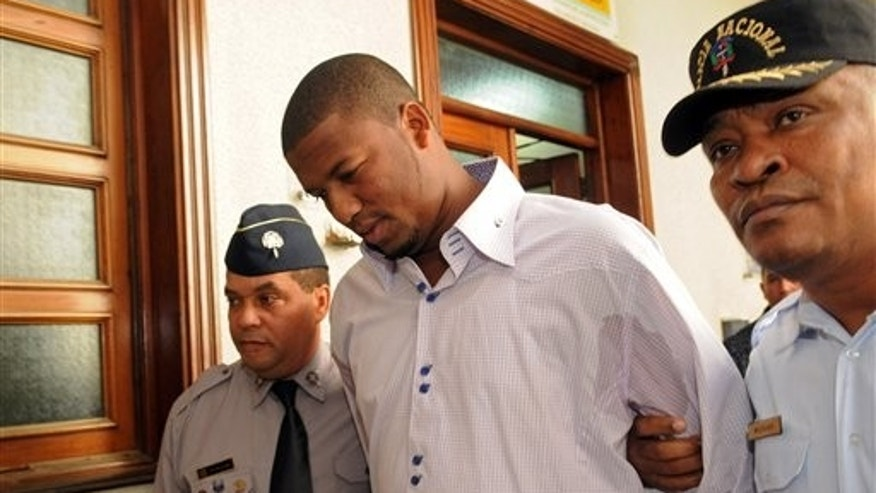 Jan. 20, 2012: Cleveland Indians pitcher Fausto Carmona, whose real name is Roberto Hernandez Heredia, is escorted by police out of court in Santo Domingo, Dominican Republic.