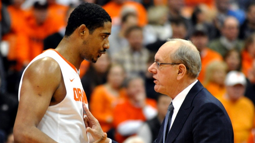 FILE - In this Jan. 15, 2011, file photo, Syracuse head coach Jim Boeheim, right, talks with Fab Melo during the first half against Cincinnati in an NCAA college basketball game in Syracuse, N.Y. Melo did not travel with the team to Pittsburgh and the university says he won't take part in the NCAA tournament due to an eligibility issue.  The school would not elaborate.  (AP Photo/Kevin Rivoli, File)