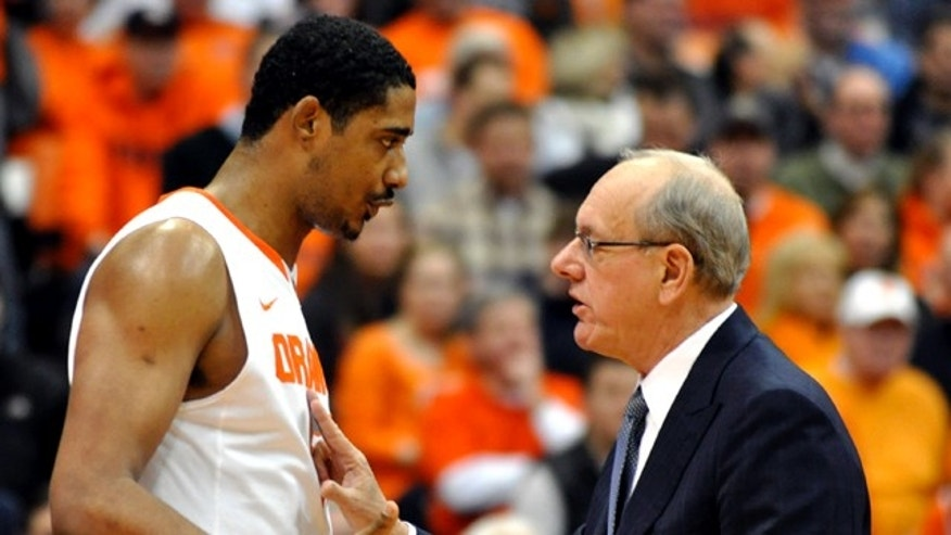 Jan. 15, 2011: FILE - Syracuse head coach Jim Boeheim, right, talks with Fab Melo during the first half against Cincinnati in an NCAA college basketball game in Syracuse, N.Y.