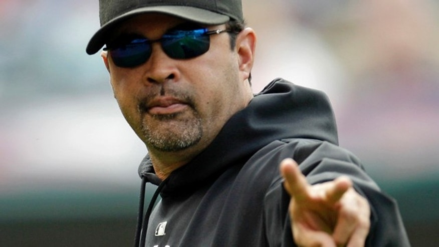 Chicago White Sox manager Ozzie Guillen acknowledges a fan during the seventh inning in the first baseball game of a doubleheader against the Cleveland Indians, Tuesday, Sept. 20, 2011, in Cleveland. (AP Photo/Tony Dejak)