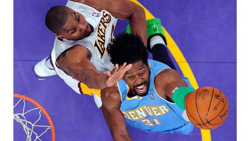 Denver Nuggets center Nene, right, of Brazil, puts up a shot as Los Angeles Lakers center Andrew Bynum defends during the second half of an NBA basketball game, Sunday, April 3, 2011, in Los Angeles. The Nuggets won 95-90. (AP Photo/Mark J. Terrill)