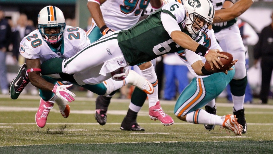 New York Jets quarterback Mark Sanchez (6) dives away from Miami Dolphins free safety Reshad Jones (20) for a touchdown during the second quarter of an NFL football game Monday, Oct. 17, 2011, in East Rutherford, N.J. (AP Photo/Julio Cortez)