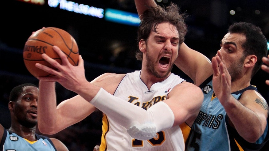 Los Angeles Lakers forward Pau Gasol, middle, grabs a rebound from Memphis Grizzlies center Hamed Haddadi, right, as Grizzlies guard Jeremy Pargo, left, looks on during the second half of an NBA basketball game, Sunday, March 25, 2012, in Los Angeles. The Grizzlies won 102-96. (AP Photo/Bret Hartman)
