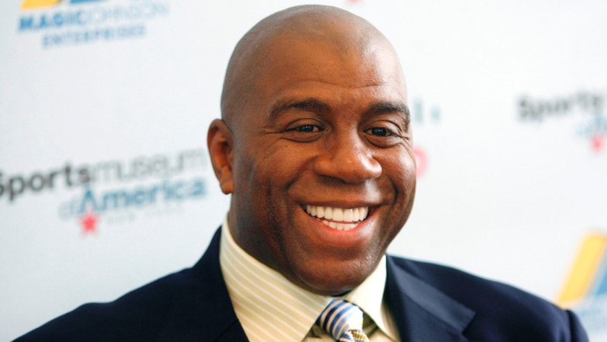 Basketball legend turned entrepreneur Magic Johnson tours the Sports Museum of America in New York, Friday, Nov. 21, 2008.  A group that includes former Lakers star Magic Johnson and longtime baseball executive Stan Kasten agreed Tuesday night March 27, 2012 to buy the Los Angeles Dodgers from Frank McCourt for $2 billion.  (AP Photo/Seth Wenig)