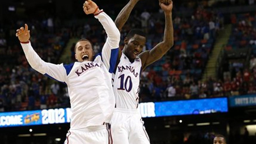 Kansas guard Tyshawn Taylor (10) celebrates with Kansas guard Christian Garrett at the end of an NCAA Final Four semifinal college basketball tournament game against Ohio State.
