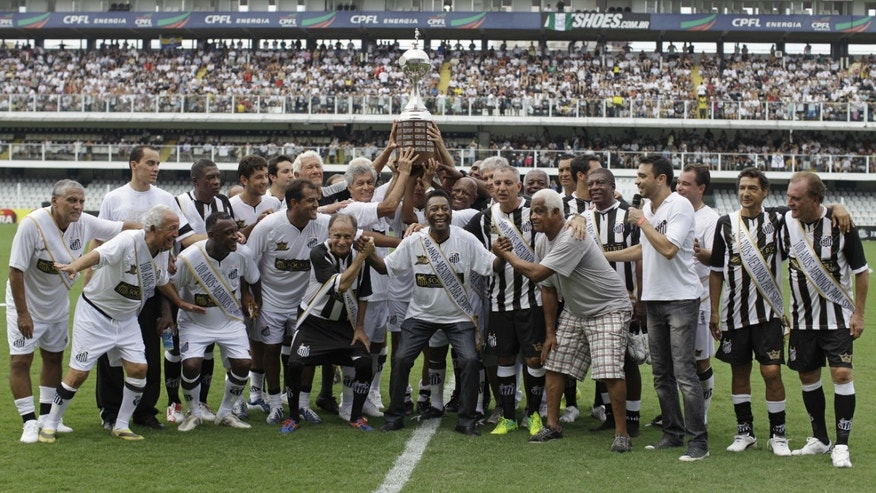"Pelé, center, with other former Santos soccer players hold up the Libertadores championship trophy during during the centennial anniversary celebration of the team in Santos, Brazil, Saturday, April 14, 2012. Santos, the Brazilian club which ruled football with ""The King"" Pele in the 1960's, turns 100 with a rich history to show, including many major titles and remarkable victories that make the club one of the most successful in football. (AP Photo/Nelson Antoine)"