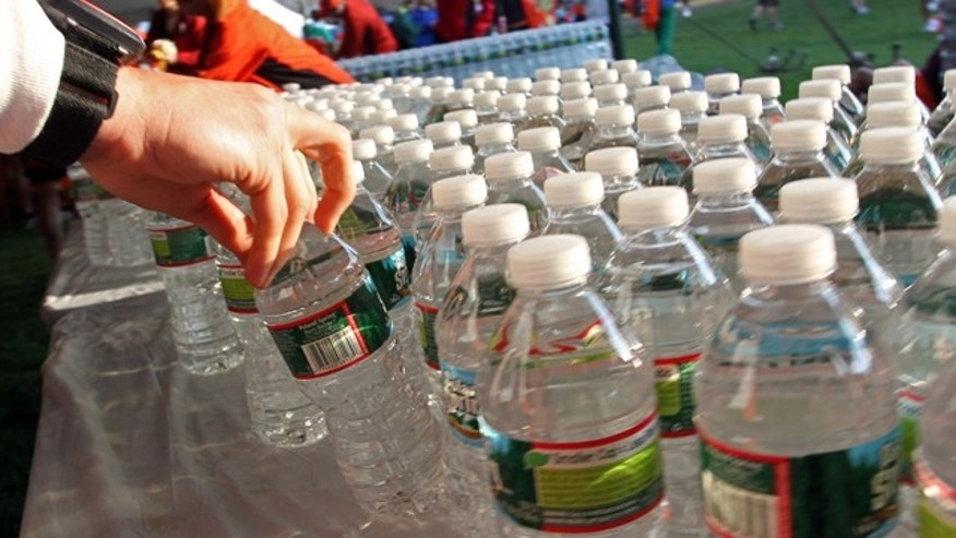 April 16, 2012: A runner grabs a bottle of water at the athlete's village prior to the start of the 116th running of the Boston Marathon, in Hopkinton, Mass. (AP)