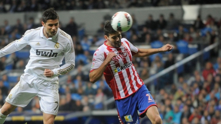 MADRID, SPAIN - APRIL 14:  Cristiano Ronaldo (L) of Real Madrid CF beats Alberto Botia to score their second goal during the La Liga match between Real Madrid CF and Real Sporting de Gijon at Estadio Santiago Bernabeu on April 14, 2012 in Madrid, Spain.  (Photo by Denis Doyle/Getty Images)