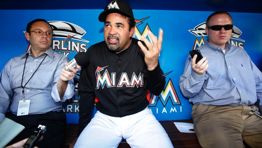 Miami Marlins manager Ozzie Guillen, center, talks to reporters before the Marlins' baseball game against the Chicago Cubs, Tuesday, April 17, 2012, in Miami. Guillen returned following a five-game suspension imposed by the team after he angered Cuban exiles by praising Fidel Castro. (AP Photo/Wilfredo Lee)