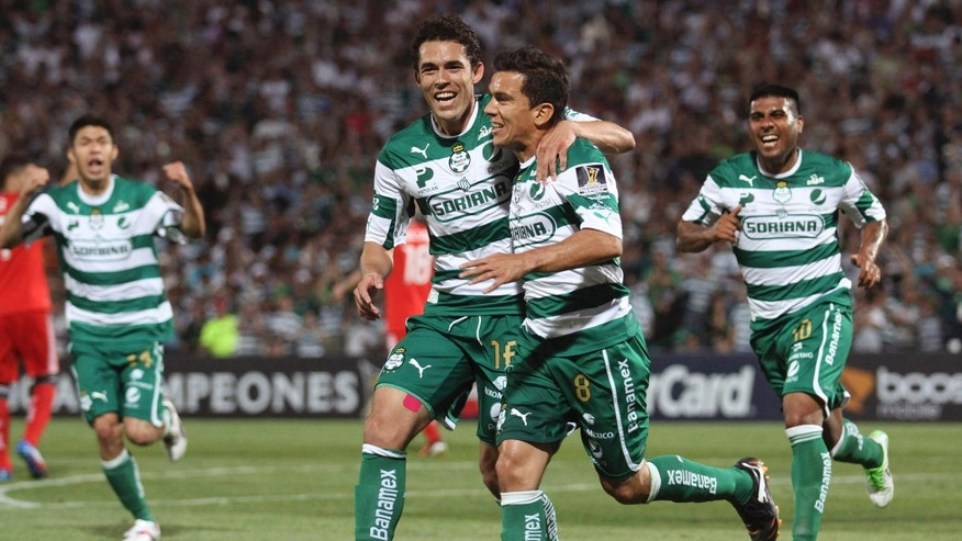 FILE - This April 4, 2012 file photo shows Juan Pablo Rodriguez, second from right, of Mexico's Santos Laguna,  celebrating with teammate Herculez Gomez after scoring against Canada's Toronto FC during a semifinal match of the CONCACAF Champions League in Torreon, Mexico. While the club has come close to success, the city has had a myriad of problems linked to the drug war. (AP Photo/Alberto Puente, File)