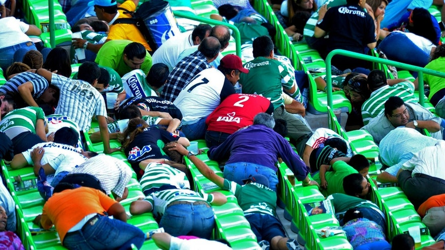 FILE - This Aug. 20, 2011 file photo shows fans of soccer club Santos taking cover between the stadium seats as they hear shooting outside the stadium Territorio Santos Modelo in Torreon, Mexico. While the club has come close to success, the city has had a myriad of problems linked to the drug war.  (AP Photo/El Siglo de Torreon) MANDATORY CREDIT