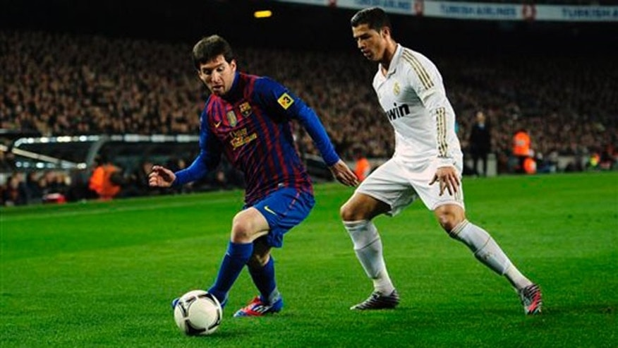 Barcelona's Lionel Messi, left, is marked by Real Madrid's Cristiano Ronaldo. January 25, 2012. (AP Photo/Manu Fernandez)