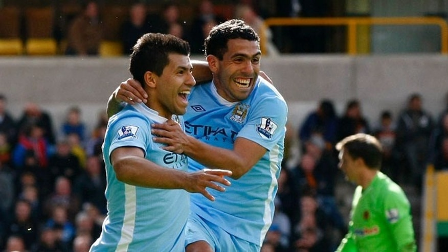 Manchester City's Sergio Aguero, left, celebrates with team mate Carlos Tevez after scoring a goal against Wolverhampton Wanderers during their English Premier League soccer match at Molineux Stadium, Wolverhampton, England, Sunday April 22, 2012. (AP Photo/Tim Hales)