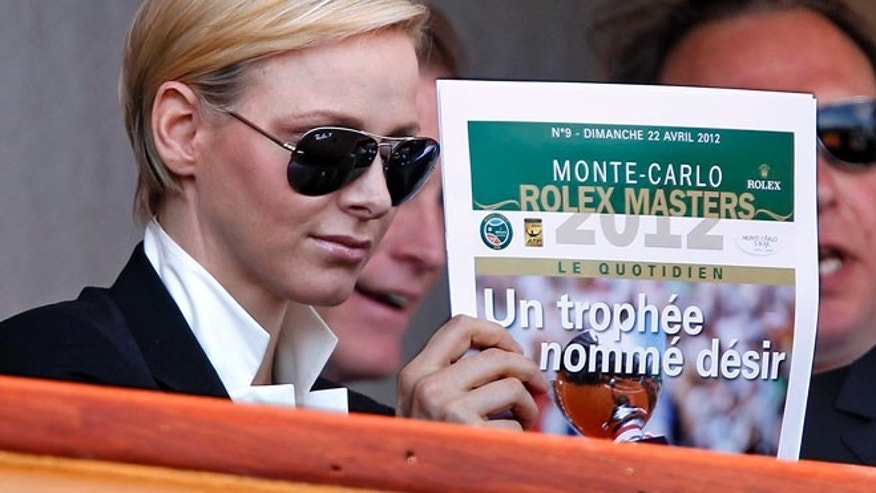 April 22: Princess Charlene of Monaco reads a Monte Carlo tennis newspaper that has a headline which reads 'A Trophy Named Desire.'