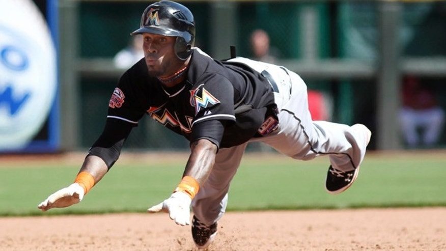 Miami Marlins' Jose Reyes (7) dives into third base during the ninth inning of a baseball game against the Cincinnati Reds on Sunday, April 8, 2012, in Cincinnati. The Reds won 6-5. (AP Photo/ Ernest Coleman)