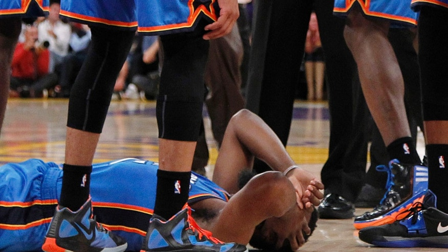 April 22: Oklahoma City Thunder players stand over teammate James Harden, lower left, after receiving a flagrant double foul from Los Angeles Lakers' Metta World Peace, who was then ejected, in the first half of an NBA basketball game in Los Angeles.