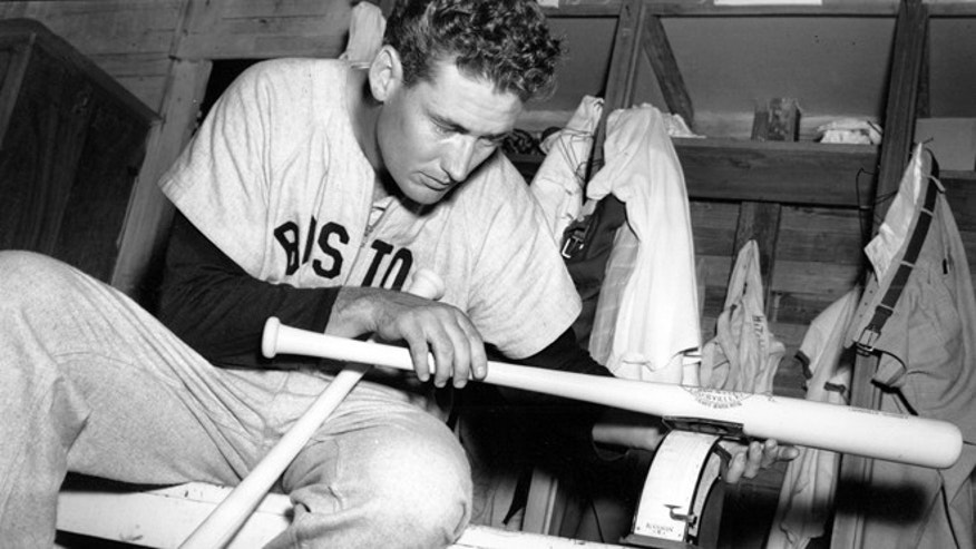 March 16, 1948: In this file photo, Boston Red Sox Ted Williams weighs one of his new 36-ounce Hickory baseball bats in the clubhouse after morning workout at spring training in Sarasota, Fla.