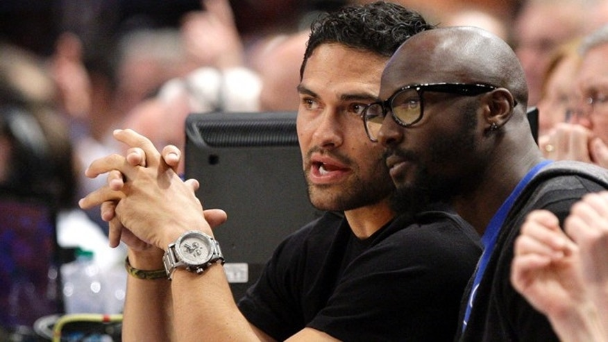 New York Jets NFL football teammates Mark Sanchez, left, and Santonio Holmes, right, watch the New York Knicks play the Los Angeles Clippers during the first half of an NBA basketball game, Wednesday, April 25, 2012, in New York.