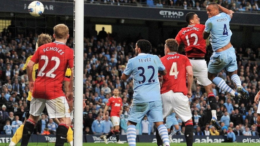 Manchester City's Vincent Kompany, right, scores against Manchester United goal during the English Premier League match at the Etihad Stadium, Manchester, Monday April 30, 2012. (AP Photo/PA, Martin Rickett)