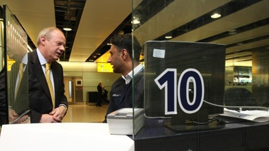May 1, 2012: Britain's Immigration Minister Damian Green, left, talks to UK Border Agency Immigration officer Shafait Ali during a visit to Terminal 3 of Heathrow Airport, London. Green says that the government is taking action to address long waits at airport immigration lines amid further criticism from an airline executive.
