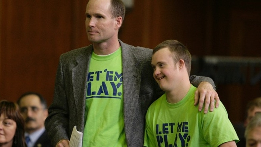 May 2, 2012: Dean Dompierre, left, and his son, Eric Dompierre, are introduced before they testify at a state Senate committee hearing in Lansing, Mich. Dompierre is supporting an age-limit waiver that would allow his son with Down syndrome to play sports next season.