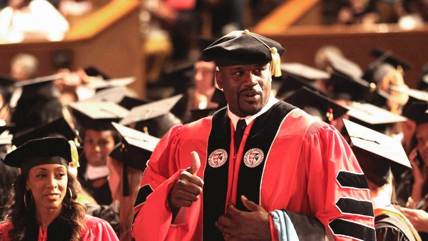 May 5, 2012: Towering over his classmates, former NBA star Shaquille O'Neal, gestures before the graduation ceremony at the James L. Knight Center in Miami.