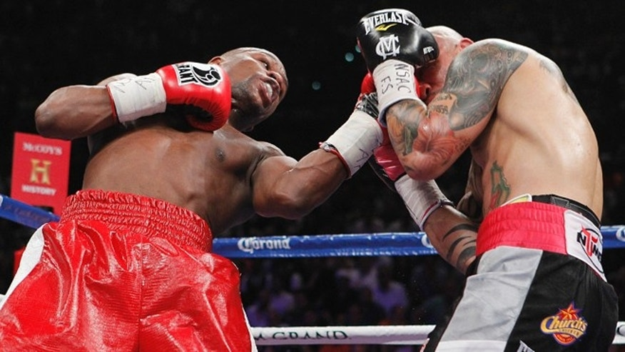Floyd Mayweather Jr., left, lands a punch against Miguel Cotto during a WBA super welterweight title fight, Saturday, May 5, 2012, in Las Vegas. Mayweather won by unanimous decision. (AP Photo/Isaac Brekken)