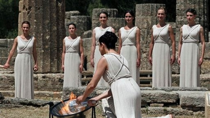 May 10, 2012: An actress as a high priestess, front, lights the Olympic flame using a concave mirror to concentrate the sun's rays during the lighting of the flame ceremony on Thursday, in Ancient Olympia, Greece.