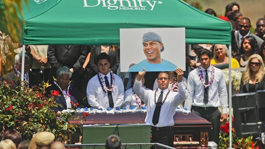 May 11, 2012: Pastor Miles McPherson, of the Rock Church and a former NFL football player, holds up a photo of Junior Seau as Seau's casket rests behind McPherson at Seau's burial Oceanside. Seau committed suicide last week.