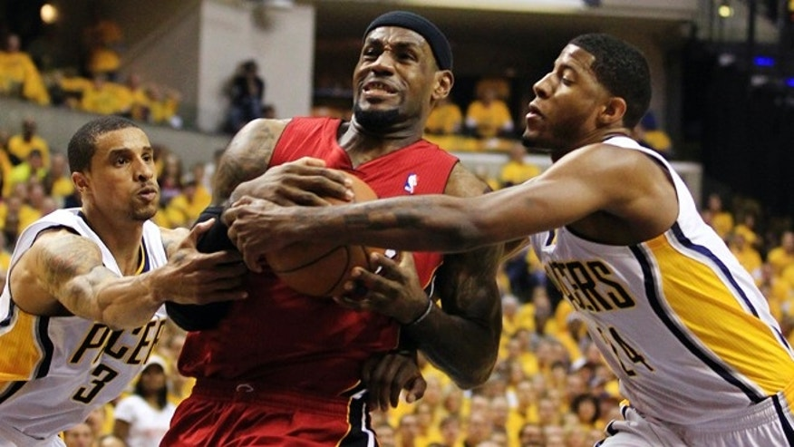 Miami Heat's LeBron James, center, goes to the basket against Indiana Pacers' George Hill (3) and Paul George, right, during the first half of Game 3 of their NBA basketball Eastern Conference semifinal playoff series, Thursday, May 17, 2012, in Indianapolis. (AP Photo/Darron Cummings)