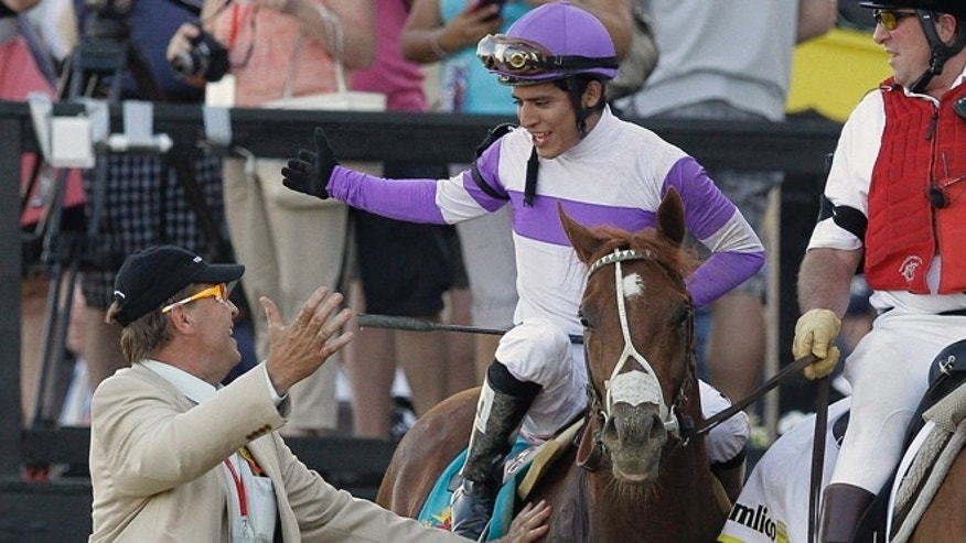 "May 19, 2012: Jockey Mario Gutierrez, aboard I'll Have Another, is greeted by horse masseuse Larry ""Thumper"" Jones, left, while outrider Clark Casey looks on after winning the 137th Preakness Stakes horse race at Pimlico Race Course in Baltimore."