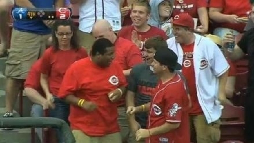 Cincinnati Reds fan Caleb Lloyd grasps one of two home run balls he caught Monday night.