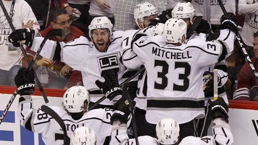 May 22, 2012: Los Angeles Kings' Mike Richards (10) shouts in celebration as teammates Jeff Carter (77), Willie Mitchell (33), Jarret Stoll (28), Alec Martinez (27), and Colin Fraser (24) converge on Dustin Penner (25), who scored the game-winner against the Phoenix Coyotes in overtime during Game 5 of the NHL hockey Stanley Cup Western Conference finals in Glendale, Ariz.