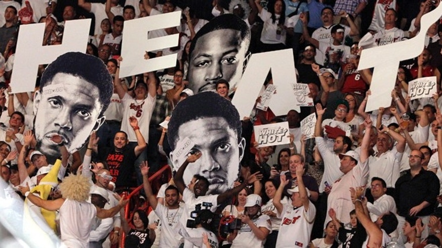 Fans hold up cutout heads of Miami Heat's Udonis Haslem, left, and Dwyane Wade, rear, during the second half of Game 5 of an NBA basketball Eastern Conference semifinal playoff series between the Heat and the Indiana Pacers in Miami, Tuesday, May 22, 2012. The Heat won 115-83. (AP Photo/Lynne Sladky)