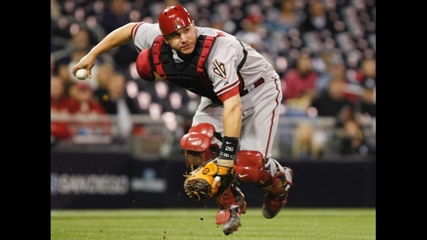 FILE - in this April 10, 2012, file photo, Arizona Diamondbacks catcher Miguel Montero fields a bunt attempt by San Diego Padres' Will Venable during a baseball game in San Diego.
