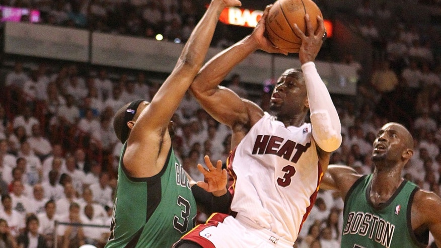 Dwyane Wade goes to the basket against Paul Pierce,left and Kevin Garnett,right during the fourth quarter of game 1 of the NBA Eastern Conference Finals between the Boston Celtics against Miami Heat at the AmericanAirlines Arena in Miami on Monday, May 28, 2012.  The Heat beat the Boston Celtics 93-79.  (AP Photo/El Nuevo Herald, David David Santiago )