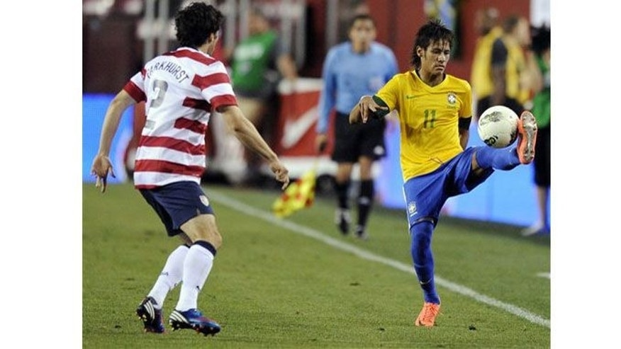 Brazil's Neymar (11) controls the ball against United States' Michael Parkhurst (2) during the second half of an international friendly soccer game, Wednesday, May 30, 2012, in Landover, Md. Brazil won 4-1. (AP Photo/Nick Wass)