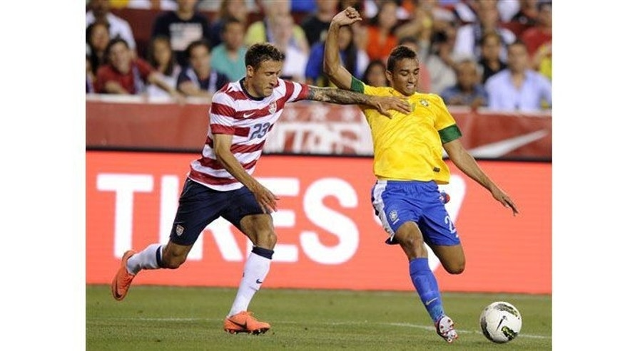 United States' Fabian Johnson (23) tries to stop Brazil's Danilo, right, during the second half of an international friendly soccer game on Wednesday, May 30, 2012, in Landover, Md. Brazil won 4-1. (AP Photo/Nick Wass)