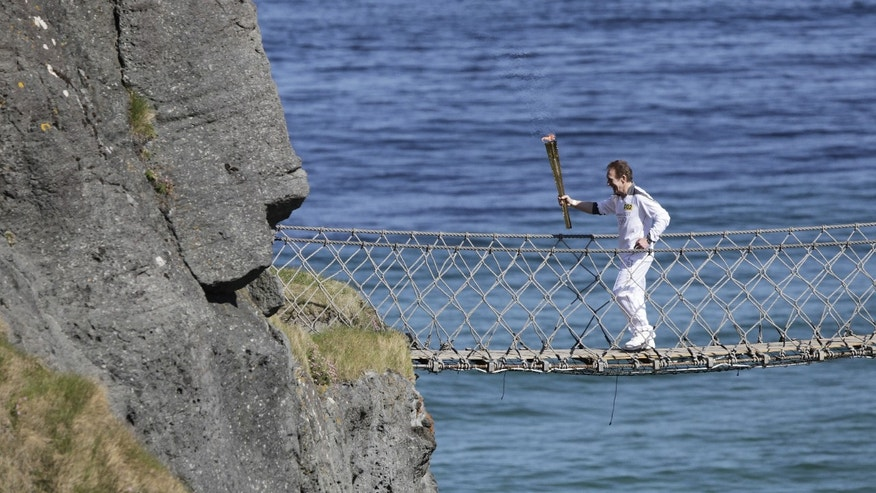June 4, 2012: Denis Broderick carries the Olympic Torch over the Carrick-a-Rede rope bridge in county Antrim, Northern Ireland.