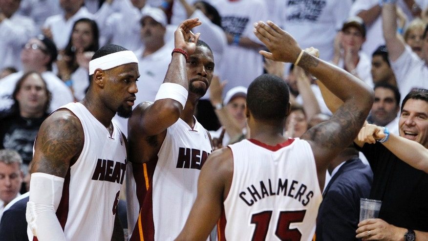 June 9, 2012: Miami Heat's Chris Bosh, center, Mario Chalmers, right, and LeBron James congratulate each other during the second half of Game 7 of the NBA basketball playoffs Eastern Conference finals.