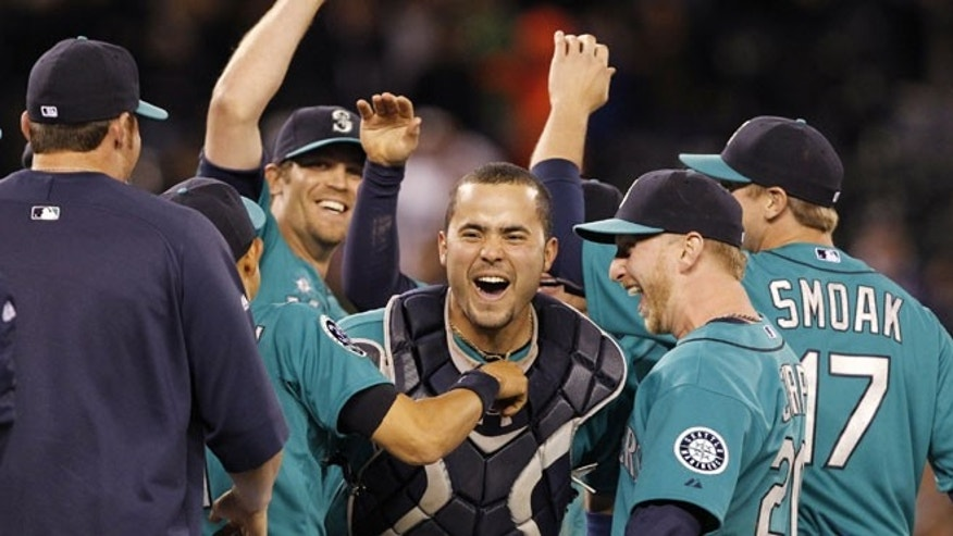 June 8, 2012: Seattle Mariners catcher Jesus Montero, center, celebrates with teammates, including closer Tom Wilhelmsen, left, after the final out against the Los Angeles Dodgers in a baseball game in Seattle.