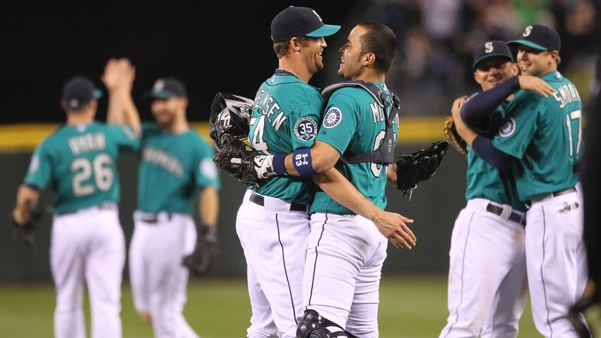 SEATTLE, WA - JUNE 08:  Closing pitcher Tom Wilhelmsen #54 of the Seattle Mariners celebrates with catcher Jesus Montero #63 after a combined no-hitter against the Los Angeles Dodgers. (Photo by Otto Greule Jr)