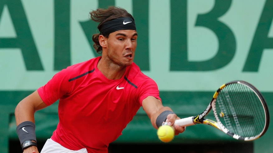 June 11, 2012: Spain's Rafael Nadal returns the ball to Serbia's Novak Djokovic during their men's final match in the French Open tennis tournament at the Roland Garros stadium in Paris.