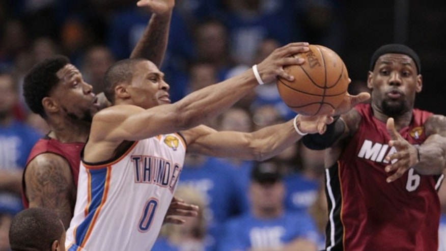 June 12, 2012: Oklahoma City Thunder point guard Russell Westbrook (0) grabs a rebound as Miami Heat power forward Udonis Haslem (40) and small forward LeBron James defend during the second half at Game 1 of the NBA finals basketball series in Oklahoma City.