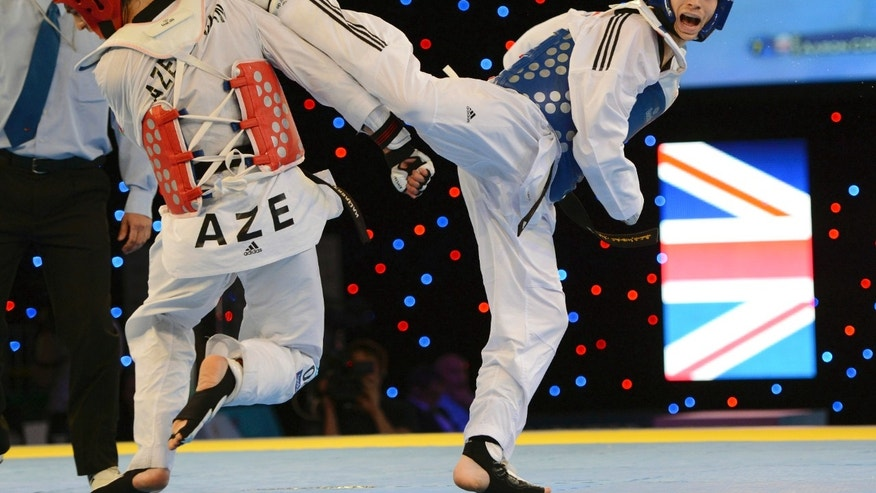 May 5, 2012: Great Britain's Aaron Cook, right, aims a kick on his way to controversially beating Ramin Azizov of Azerbaijan in the final of the Men's 80kg competition during the European Taekwondo Championships, at the Manchester Regional Arena, Manchester, England.